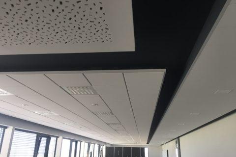 Abgehängte Akustikdecken im Büro mit Randfries und indirekter Beleuchtung auf unterschiedlichen Deckenhöhen